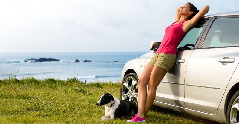 Kvinna och hund utanför en bil vid havet