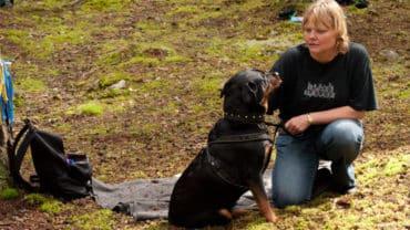 Kvinna med rottweiler i spårskogen