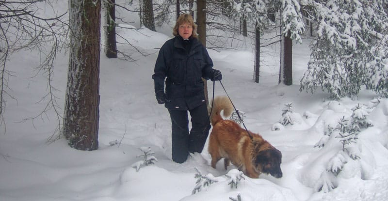 Elisabeth med hunden Astra i snöiga skogen