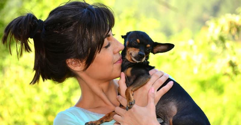 Kvinna håller en liten hund  i famnen