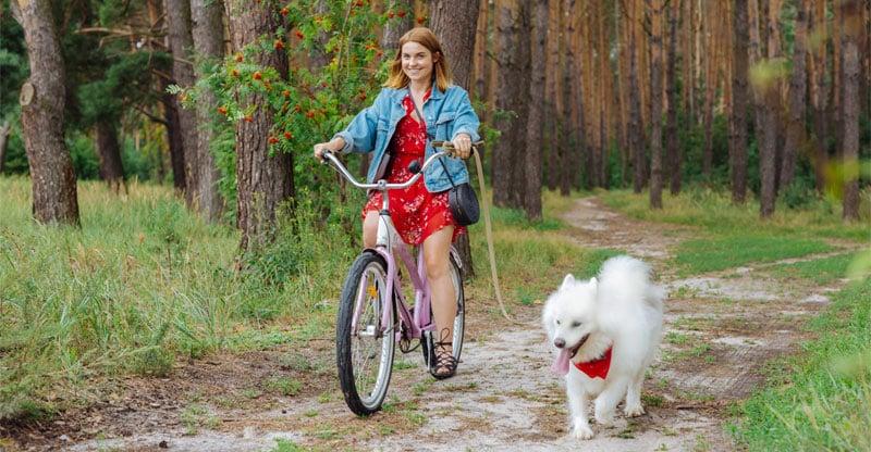 En ung kvinna cyklar med sin hund i skogen